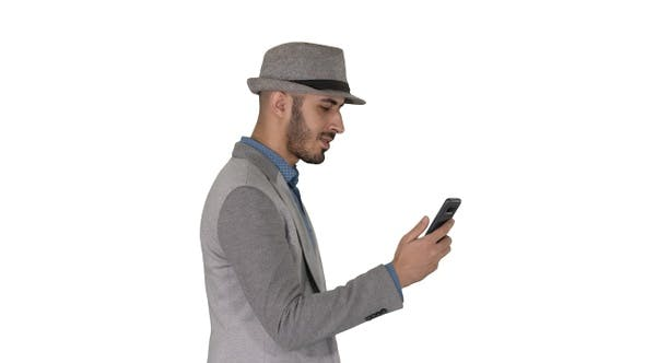 Thumbnail for Man walking with a phone and serfing internet on white background.