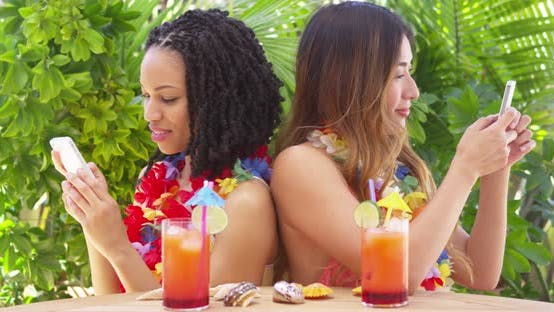 Thumbnail for Black and Asian best friends on vacation using mobile phones