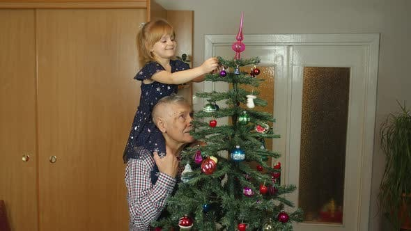 Children Girl with Elderly Grandparent Decorating Artificial Christmas Pine Tree at Oldfashion Home