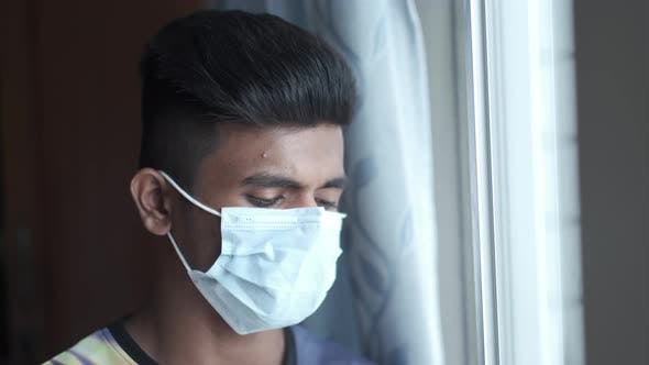 A Young Man with Protective Mask Looking Through Window
