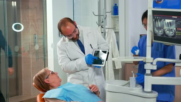 Thumbnail for Dentist in Dental Office Examining X-ray Image on Tablet