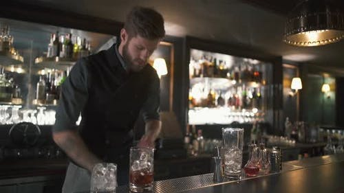 Handsome Bartender Adding Big Cubes of Ice Making a Whiskey Cocktail in Beautiful Modern Bar