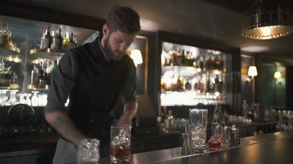 Thumbnail for Handsome Bartender Adding Big Cubes of Ice Making a Whiskey Cocktail in Beautiful Modern Bar