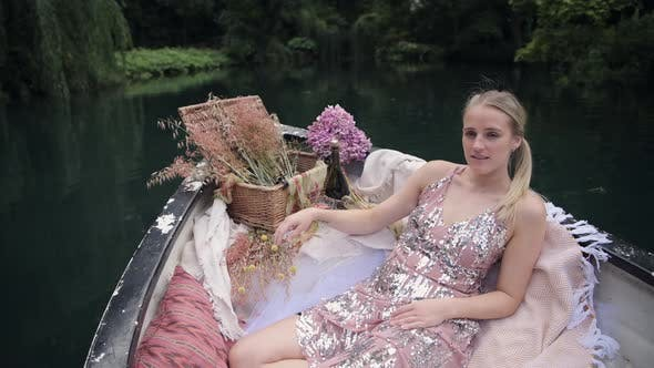 Pretty Woman In Glittery Dress Sitting On A Boat Floating In The Calm Lake - medium full shot