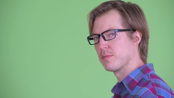 Thumbnail for Closeup Profile View of Young Handsome Hipster Man Looking at Camera