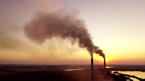 Pollution the atmosphere. Two factory pipes throw dirty emissions.