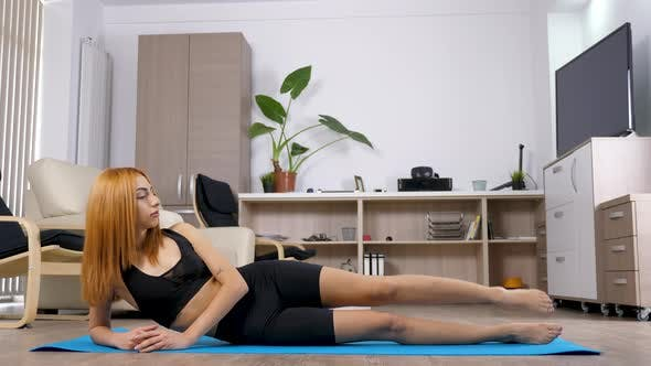 Thumbnail for Woman Lying on the Floor on a Blue Mat Stretches Her Legs
