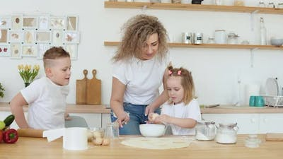 Daughter and Mother Break an Egg in a Bowl