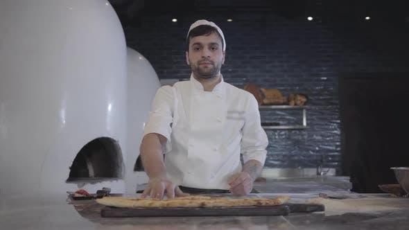 Thumbnail for Portrait of Chef in White Uniform Demonstrating Freshly Baked Fatayer Lying on the Wooden Board