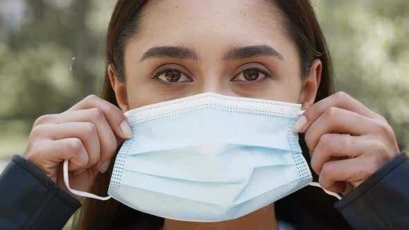 Young Woman Putting On Protective Face Mask Posing Outdoors