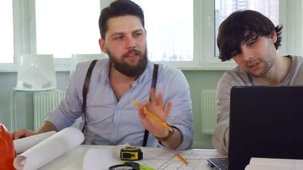 Architects Discuss Something on Laptop