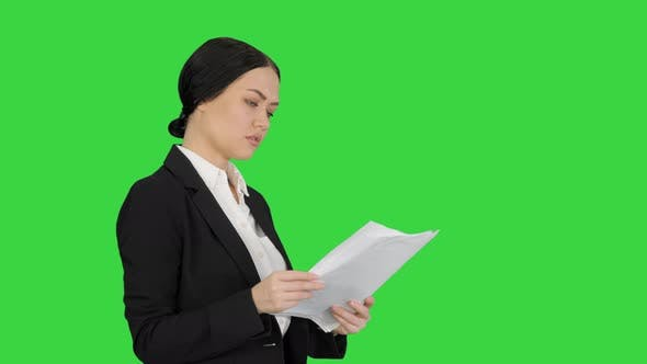 Thumbnail for Serious Cute Businesswoman Reading Documents on a Green Screen, Chroma Key
