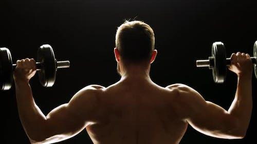 Rückansicht Bodybuilder Heben einer Hantel.
