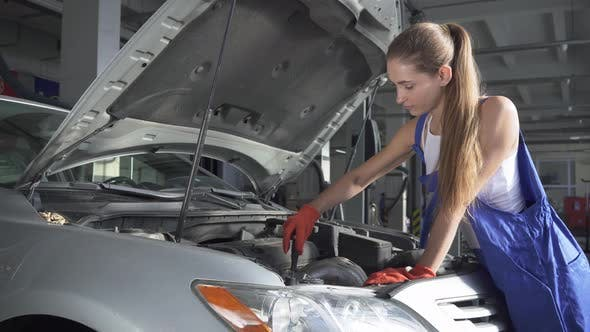 Thumbnail for Beautiful Girl in Uniform Turns a Screwdriver in a Car Engine. Car Service, Repair, Maintenance and