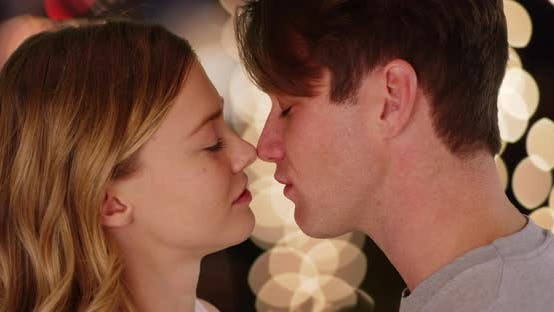 Thumbnail for Close up of couple kissing outside at night against background of bokeh lights
