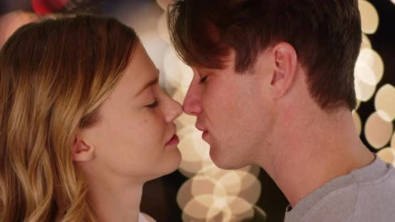 Close up of couple kissing outside at night against background of bokeh lights