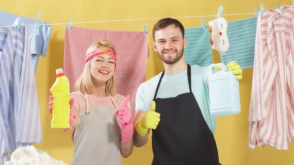 Thumbnail for Happy couple holding bottles with cleaner liquid for washing clothes