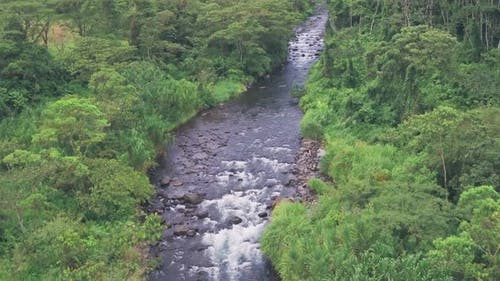 River through tropical rainforest at Arenal Volcano National Park, Costa Rica. Aerial drone view