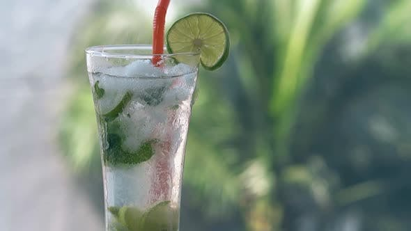 Thumbnail for White Sugar Pours Into Glass with Cold Mojito Cocktail