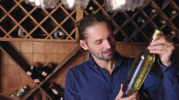 Smiling Man With Bottle Of Wine In Cellar At Winery Restaurant