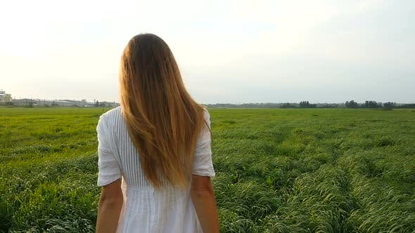 Thumbnail for Beautiful Young Woman in White Dress Walks on the Green Field. Wind Blowing Hair