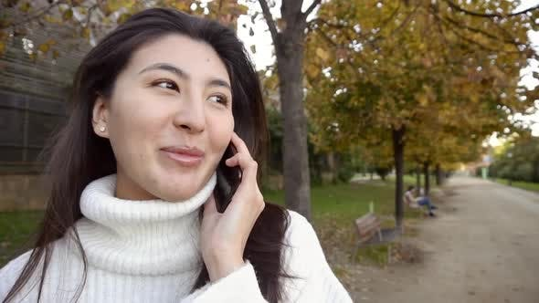 Asian Pretty Girl Wearing White Sweater Talking By Smartphone and Walking in Park.