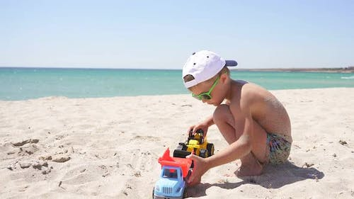 Boy Dressed in Sunglasses and a Baseball Cap Plays Cars on a Sandy Beach Against the Beautiful Sea