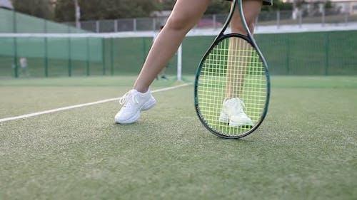 Girl turns a racket on a tennis court