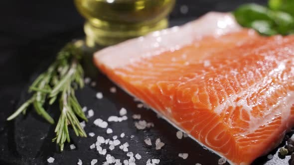 Cover Image for Spices Fall on a Raw Salmon Steak. Raw Salmon Red Fish with Pepper and Salt.