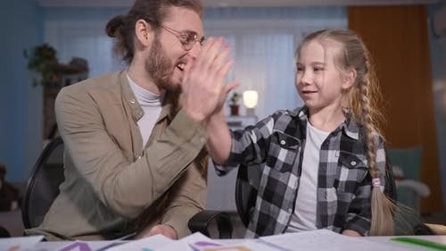 Father Helps His Pupil Daughter During Homework in Front of the Camera Parent with Girl Show Thumbs
