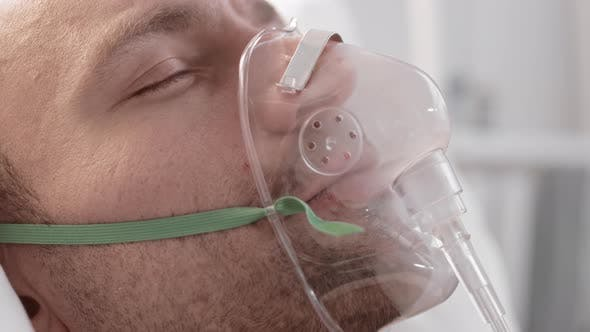 Man Breathing with Oxygen Mask