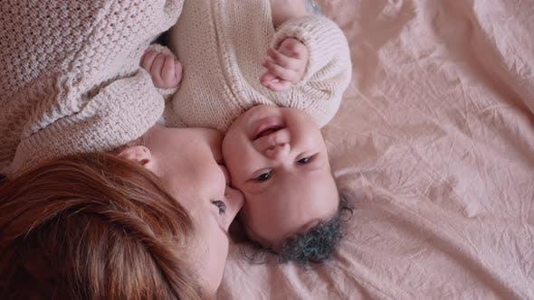 Eine Frau küsst ihre neugeborene Tochter