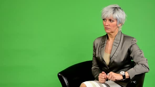 Thumbnail for Business Middle Aged Woman Sits and Waits (Looks at Watch) and Leaves - Green Screen - Studio