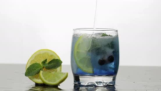 Thumbnail for Pour Water in a Glass with Leaves of Mint, Lime, Lemon, Currants, Ice