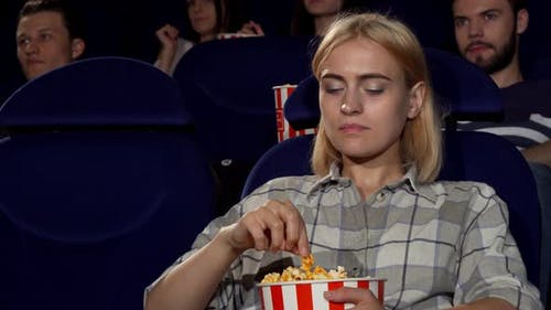 Attractive Female Eating Popcorn at Movie Premiere at the Cinema