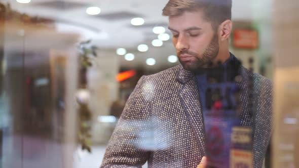 Man Looks at a Shop Window with Clothes