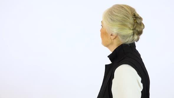 Thumbnail for An elderly woman looks around - white screen studio