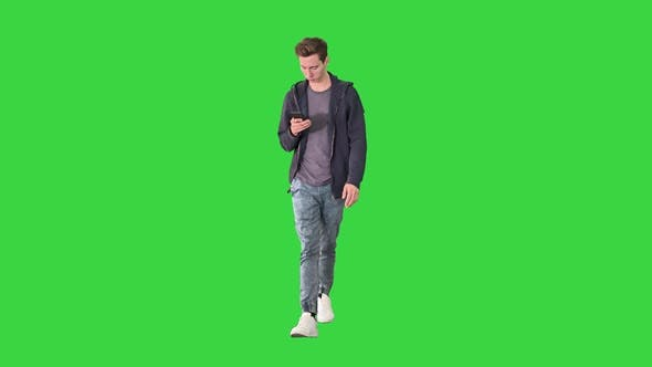 Young Man in Casual Clothes Text Messaging on Cell Phone and Walking on a Green Screen, Chroma Key.