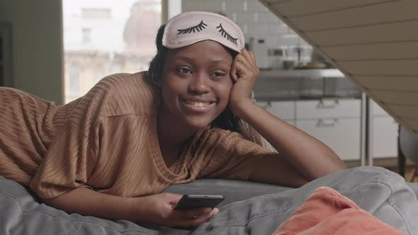 Smiling African American Woman Watching TV at Home