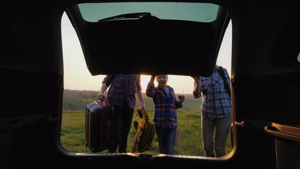 Cover Image for The Family with the Child Is Going on a Trip, Together They Put the Bags in the Trunk of the Car