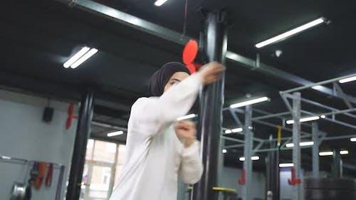 Junge muslimische Frau konzentriert sich auf das Boxen einer sportlichen Frau Hijab kämpft gerne im Fitnessstudio
