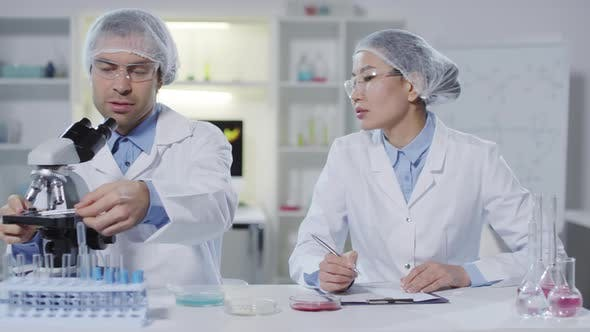 Thumbnail for Scientist Looking at Sample under Microscope as Colleague Making Notes