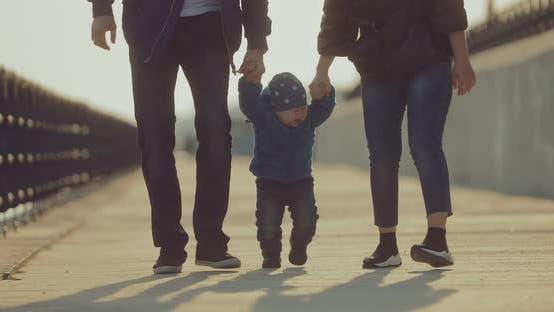 Petit garçon marche avec ses parents