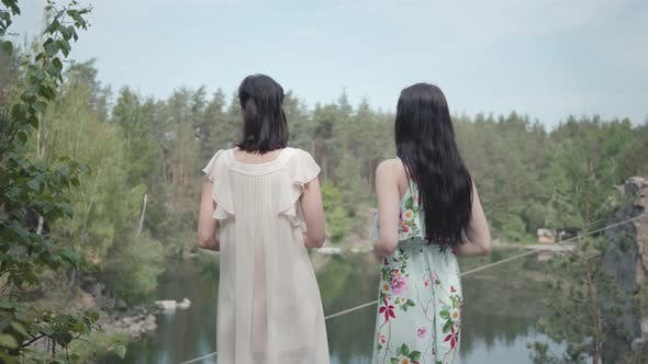 Thumbnail for Portrait Two Charming Young Women Wear Summer Dresses Standing in the Top of Rock and Looking