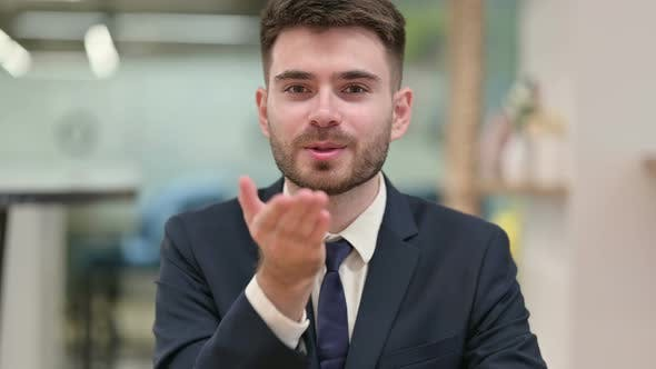 Young Businessman Giving Flying Kiss