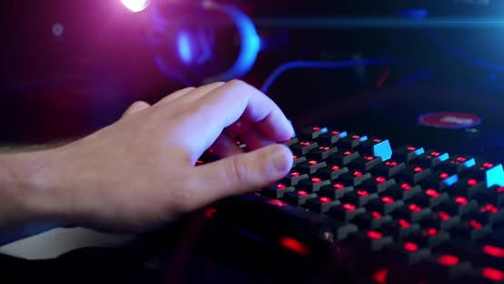 Close-up on the Hands of the Gamer Playing in the Video Game Using Keyboard Background with Cool