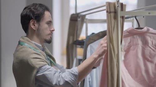 Young Confident Fashion Designer Looking at Collection on Hanger Taking Shirt Thinking
