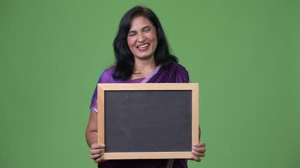 Thumbnail for Mature Happy Beautiful Indian Woman Smiling While Showing Blackboard