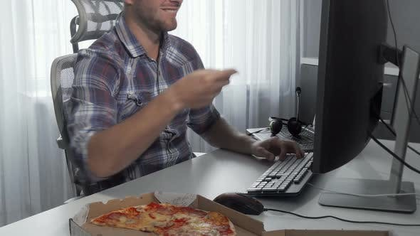 Thumbnail for Handsome Man Enjoying Tasty Pizza While Working on a Computer