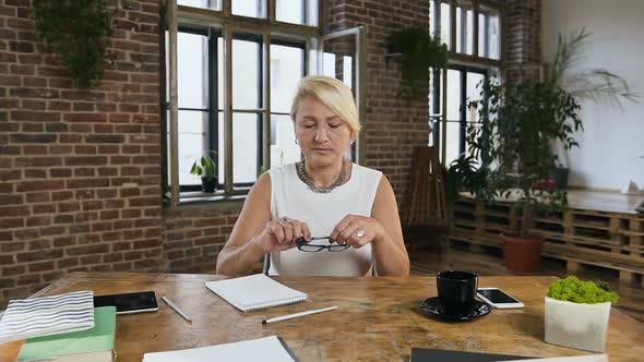 Thumbnail for Business Lady is Sitting at Table Wearing Glasses Working Developing